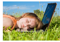 a laptop in the grass with a woman resting her head on the keyboard