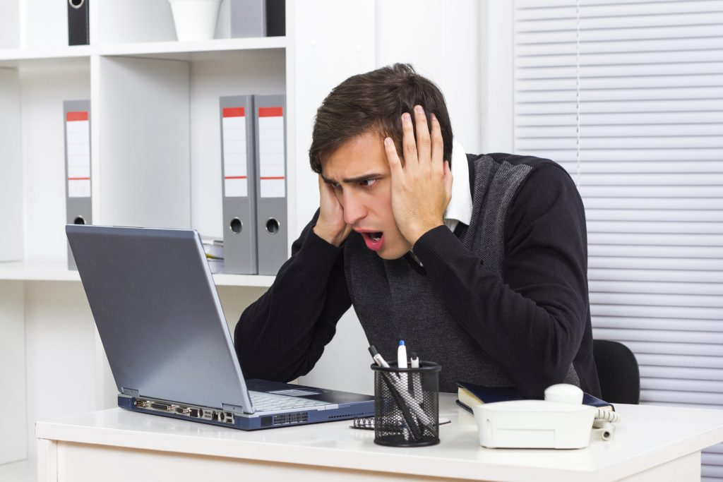 a businessman stares in disbelief with his head in his hands at a laptop