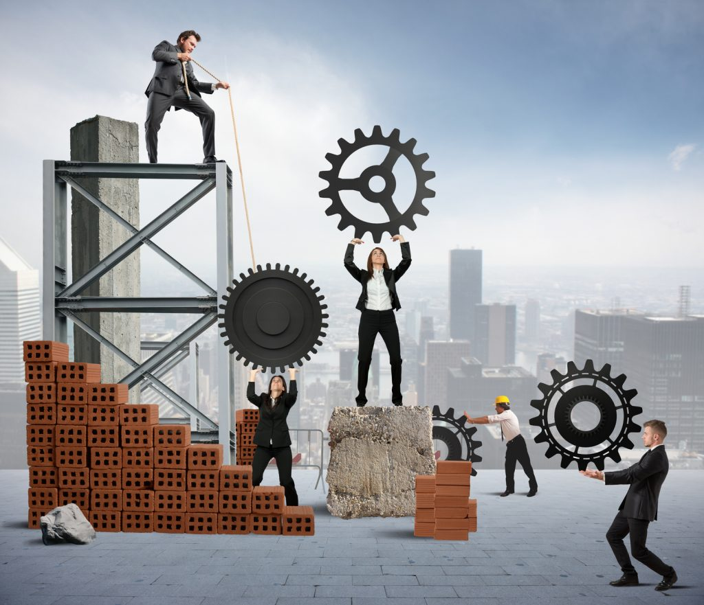 business people working with gears of exaggerated sizes