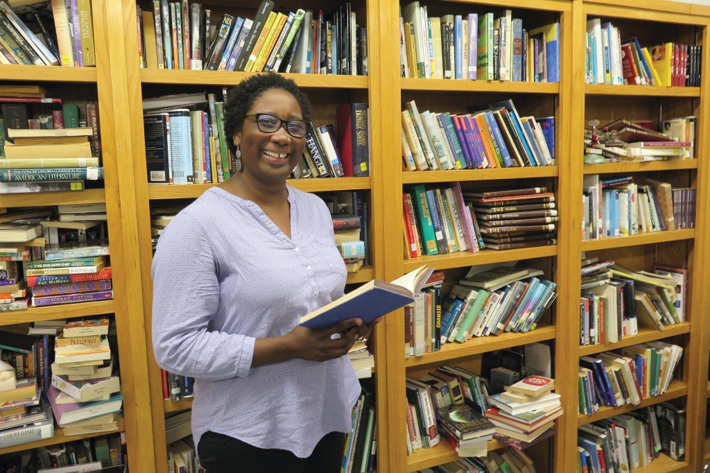 Raemona Taylor standing in front of bookcases with open book