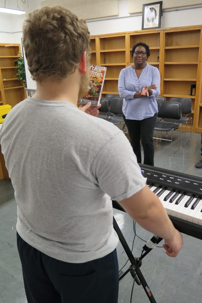 Boy playing electronic keyboard at Woodland Hills detention center as Raemona Little Taylor looks on.