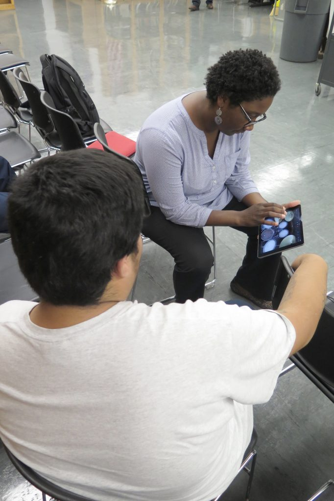 Raemona Little Taylor works with a boy on an tablet in a detention center