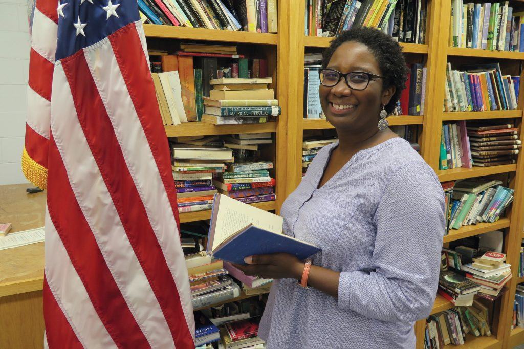 Raemona Taylor in front of bookshelf with American flag