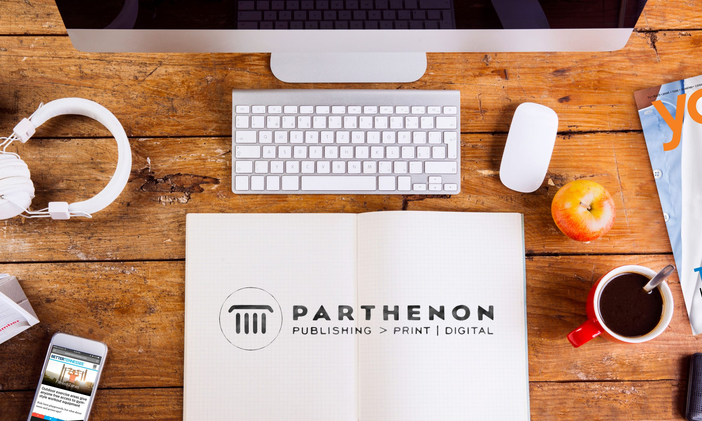 Computer, smart phone and stationery on a work surfaced branded with Parthenon Publishing's logo