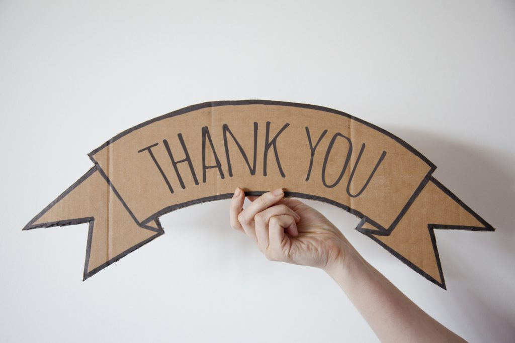 "A hand holding up a cardboard sign with the words ""Thank you"""