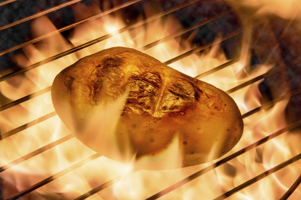 Hot potato on grill with flames