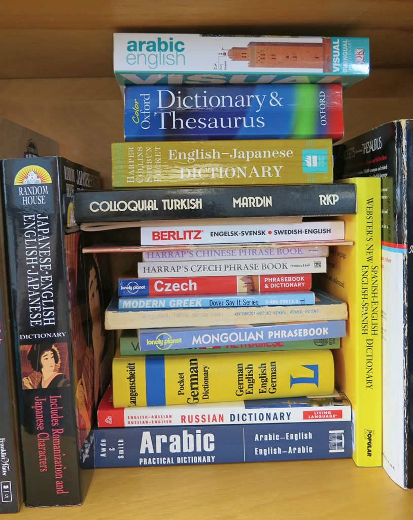 Dictionaries and workbooks in several different languages on a bookshelf.