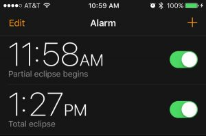 A screenshot of an iphone with alarms enabled for the eclipse