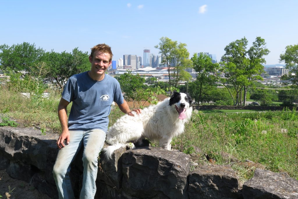 zach richardson of nashville chew crew with sheep with view of nashville skyline