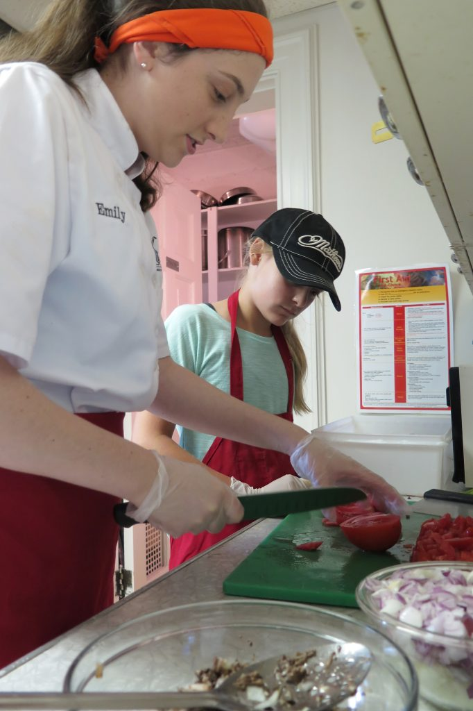 Emily mentors a young volunteer chef