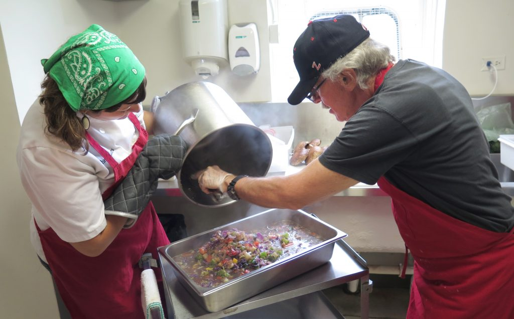 Chef and volunteer pouring soup out of pot